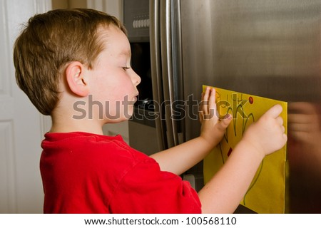Child putting his art up on family refrigerator at home - stock photo