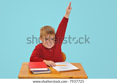 Child raising hand at school - stock photo