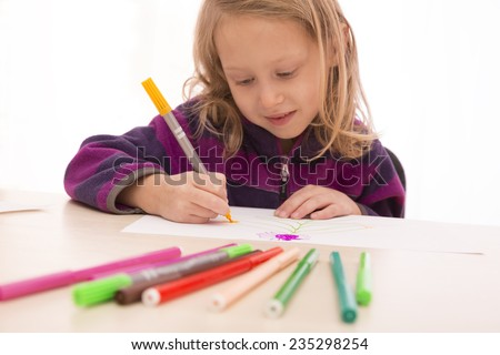 Child rapt with drawing. Child draws the picture using set of colored pens. Focus on hands, pens on the foreground and face are blurred.