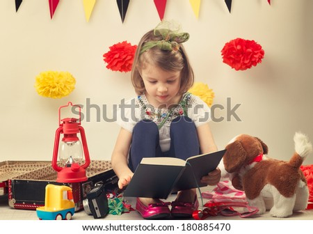 Child read a story near the suitcase with toys - stock photo