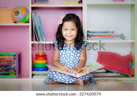 Child read, cute little girl is smiling and reading a book and sitting on floor - stock photo