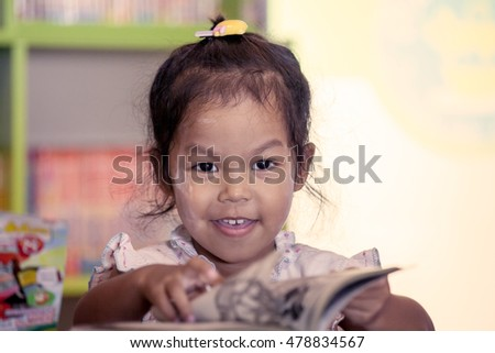 Child read, cute little girl reading a book in the library in vintage color tone