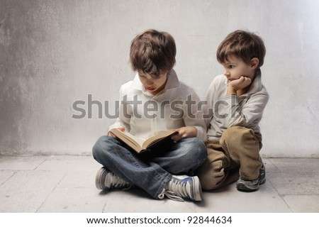 Child reading a book and little brother observing him - stock photo