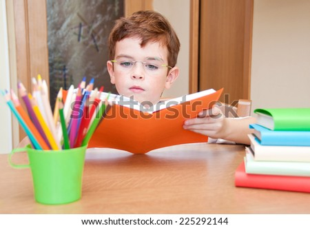 Child reading a book at a desk - stock photo
