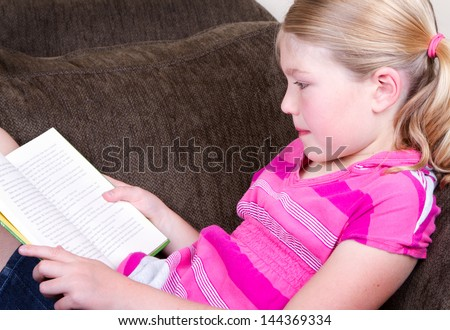 Child reading a book while relaxing or sitting on couch