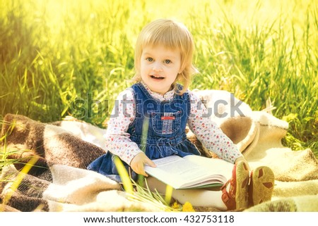 Child reading book in park. Portrait of cute little girl sitting on picnic blanket holding big book in hands. Little girl looking at pictures and learning to read. - stock photo
