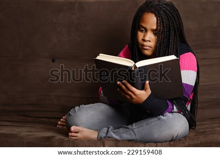 child reading book sitting on couch - stock photo