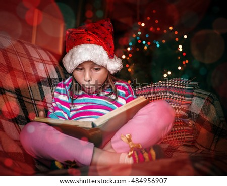 Child reads a book at Christmas.