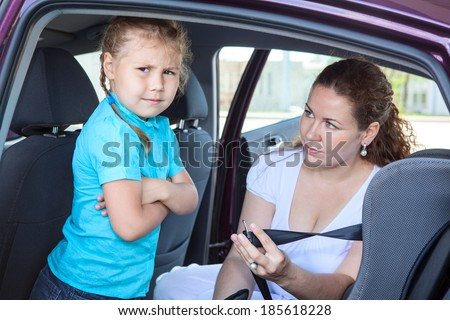 Child refusing to seat into infant car safety seat - stock photo