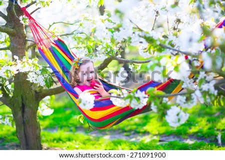 Child relaxing in hammock. Little girl playing in a blooming sunny cherry garden with white flowers. Kids having fun eating apple for healthy snack on spring vacation in a farm with fruit orchard. - stock photo