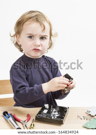 child repairing computer part. studio shot in light grey background