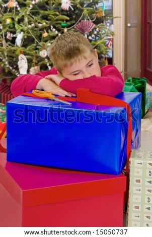 Child resting after wrapping Christmas gifts - stock photo