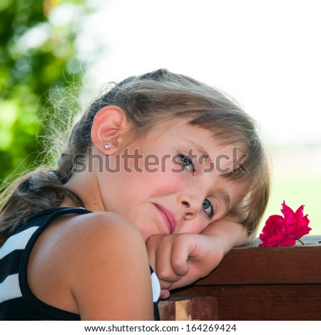 Child resting her head after playing hard out on the backyard deck. - stock photo