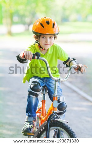 Child rides bike outdoors dressed in a colourful safety helmet and fleece green jacket - stock photo