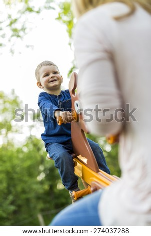 Child rides seesaw happily with his parent and smiles while in the air - stock photo