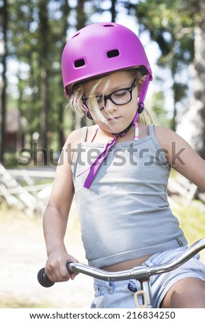 Child riding a bike with helmet and specs - stock photo