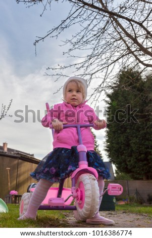 child riding a tricycle in the backyard