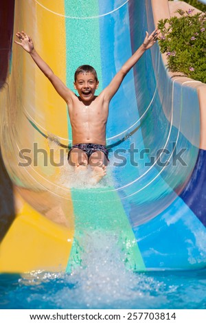 Child rolling with waterslides. Happy boy swimming - stock photo