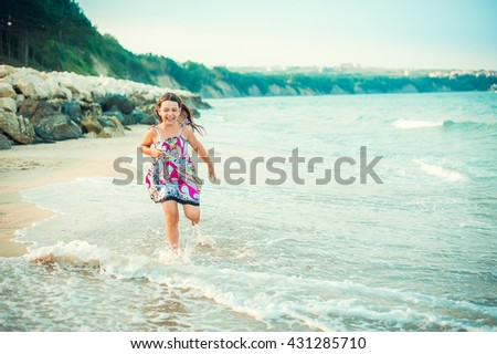 Child running along the seacoast. Girl in a colorful dress walking on the beach - stock photo