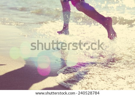 Child running at the beach, runner has motion blur. Focus on sand - stock photo
