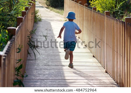 Child running on a wooden bridge or boardwalk in nature.