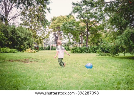 child running with blue balloon