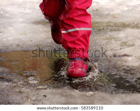 child runs through the puddles at the end of winter, beginning of spring thaw