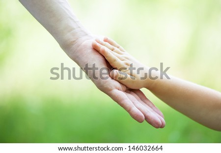 Child's and gather's hands holding together on light green background