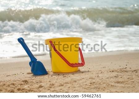 child's beach bucket and shovel on seacoast. - stock photo