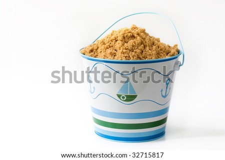 Child's beach pail full of sand - stock photo