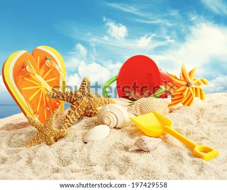 Child's beach toys in the sand at the beach - stock photo