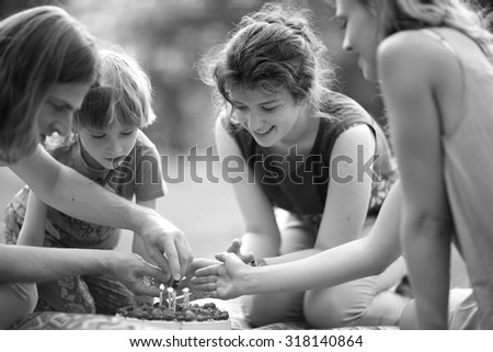 Child's birthday celebration, lighting candles on a cake  - stock photo