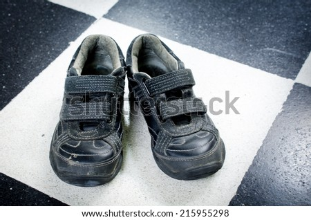 Child's black shoes on a white and white floor background,used and dirty