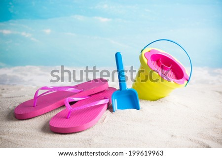 Child's bucket, spade and flip flops on tropical beach against blue sky