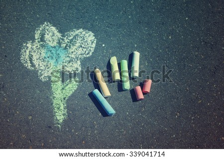 Child's drawing of  flower and colorful chalks on a street. Crayons on asphalt - stock photo