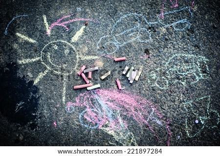 Child's drawing of sun and colorful chalks on a street - stock photo