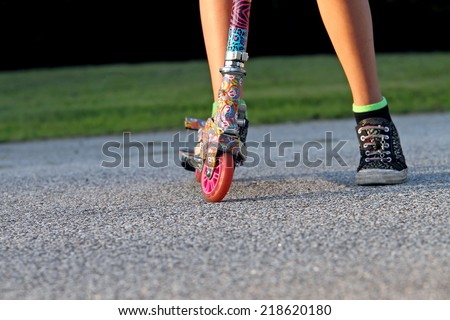 Child's feet on scooter. - stock photo