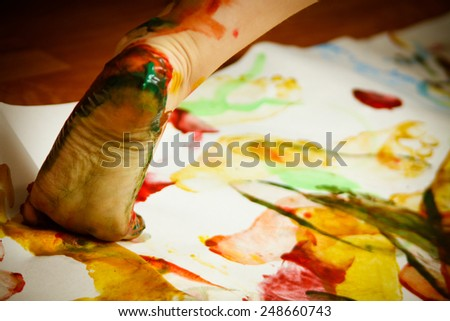 Child's foot smeared with paints