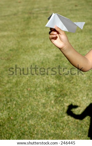 Child's hand about to through a paper plane. - stock photo