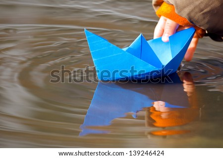 Child's hand and blue paper boat in water in spring - stock photo