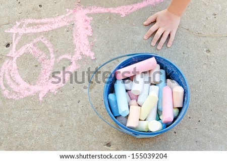 Child's hand and pail of  chalk on sidewalk - stock photo