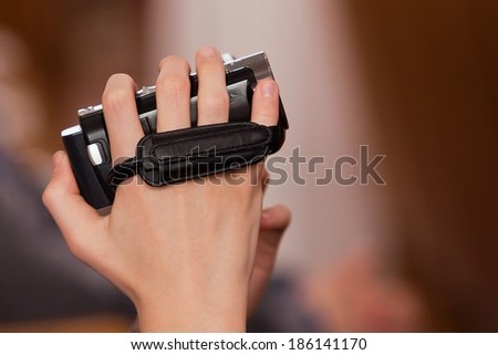 Child's hand holding a camcorder - stock photo