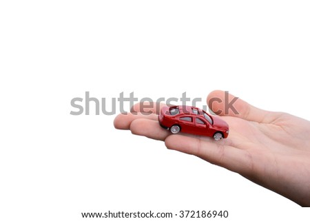 Child's hand holding a red car on a white background