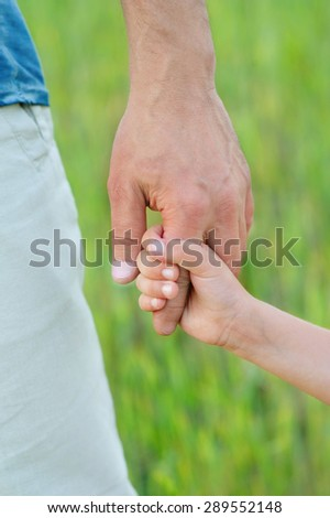 Child's hand holding on to a man's hand. Child's hand. Man's hand. - stock photo