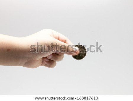 child's hand holding the coin - stock photo
