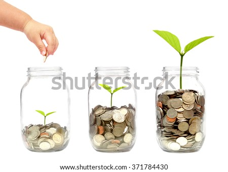 child's hand putting a golden coin into a bottle with a green plant growing on coins  - stock photo