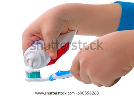 Child's hand squeezes the toothpaste on the toothbrush