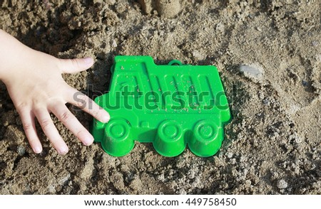 Child's hand touches a toy lorry, truck in the sandbox. Bright plastic toys in the sandbox or on the beach. Sandbox, background, children, hand, car, auto, buy, purchase, business. - stock photo