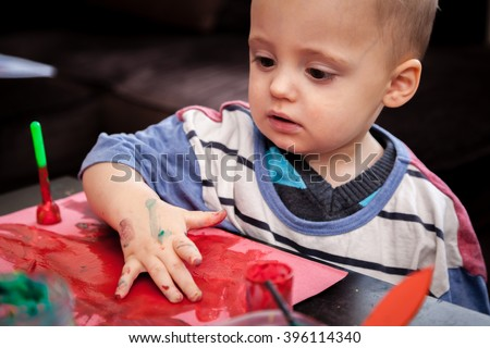 Child's hand with colored fingers from using paint - stock photo