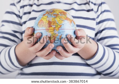 child's hand with globe - stock photo